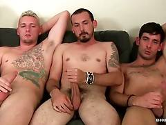 Cute horny guys sit together on one couch and play with their cocks.